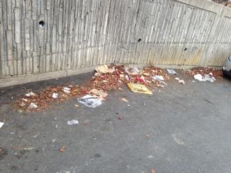 På utsiden av muren rundt blokkene flyter søppelet...